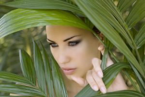 Sexy beautiful woman hiding behind the palm leaves like a panther in the tropical forest in India. Portrait of beautiful caucasian stylish young woman with smokey eyes wildness